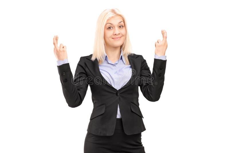 摆在与手指的年轻白肤金发的女实业家为运气横渡了 免版税图库摄影