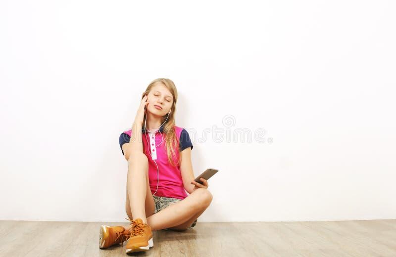 摆在与手机的偶然成套装备的微笑的少年女孩,显示情感,做滑稽的面孔 查出的空白背景 免版税图库摄影