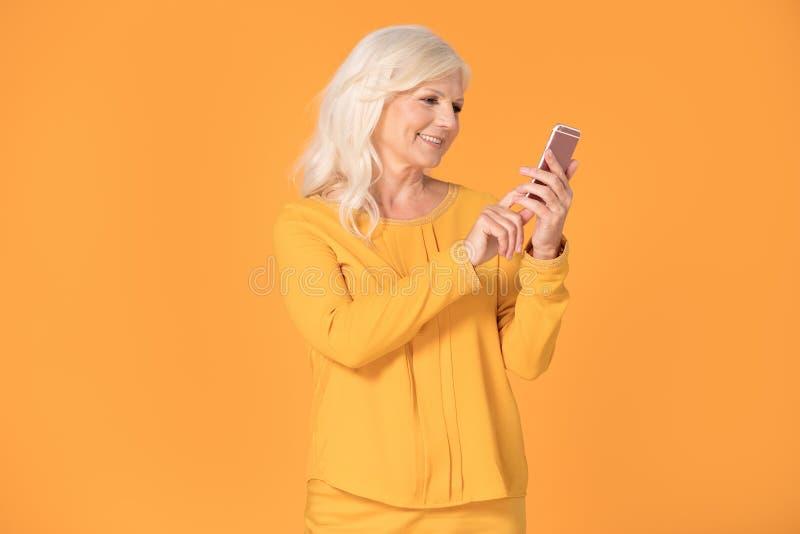 摆在与手机的资深妇女 库存照片