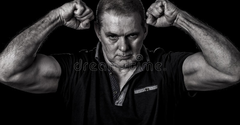摆在与握紧拳头和他的二头肌的一个不剃须的人的粗砂图象被屈曲 库存图片