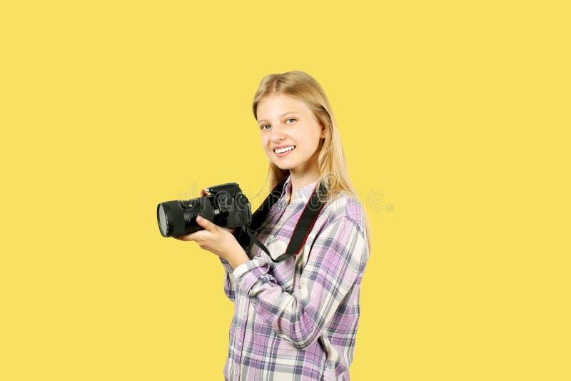 摆在与数字式SLR照片照相机,巨大的变焦镜头的逗人喜爱的少年女孩,被束缚她的脖子 被隔绝的黄色背景 库存照片