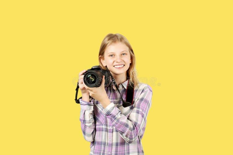 摆在与数字式SLR照片照相机,巨大的变焦镜头的逗人喜爱的少年女孩,被束缚她的脖子 被隔绝的黄色背景 免版税库存图片