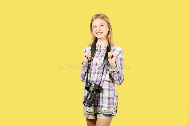 摆在与数字式SLR照片照相机,巨大的变焦镜头的逗人喜爱的少年女孩,被束缚她的脖子 被隔绝的黄色背景 免版税库存照片