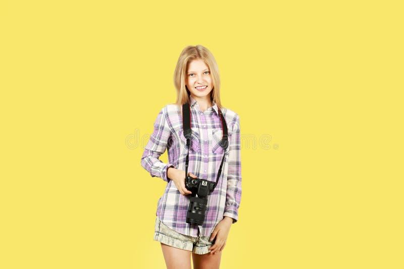 摆在与数字式SLR照片照相机,巨大的变焦镜头的逗人喜爱的少年女孩,被束缚她的脖子 被隔绝的黄色背景 图库摄影