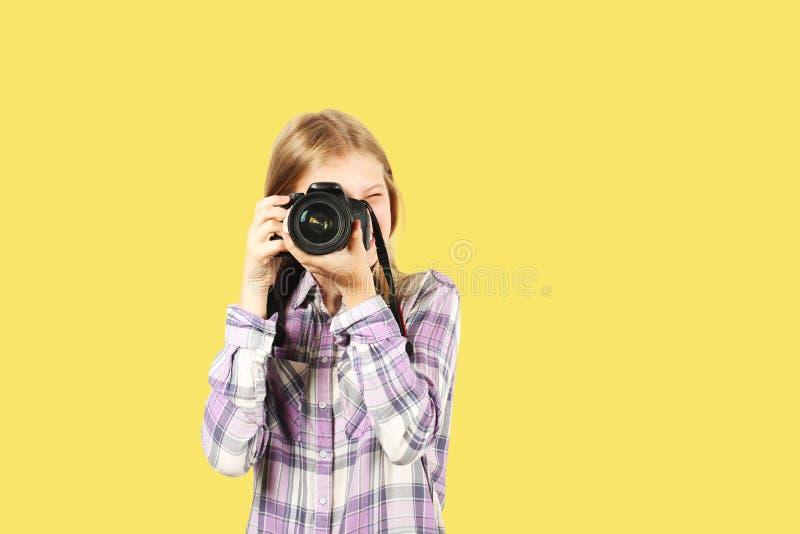 摆在与数字式SLR照片照相机,巨大的变焦镜头的逗人喜爱的少年女孩,被束缚她的脖子 被隔绝的黄色背景 库存图片