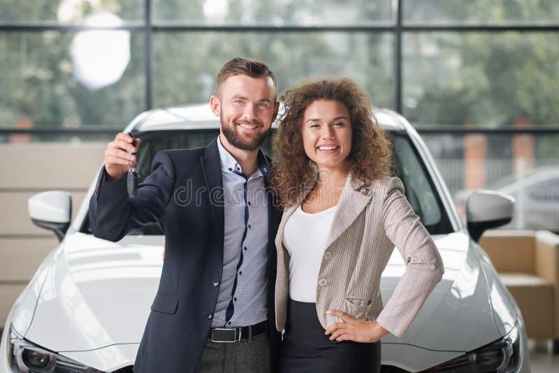 摆在与新的白色汽车和钥匙的愉快的夫妇 库存图片