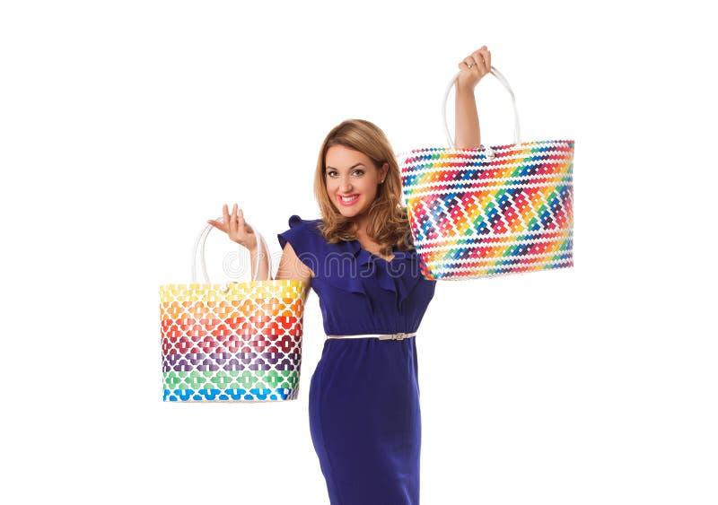 摆在与明亮的大手提袋的蓝色礼服的俏丽的妇女 查出 免版税库存照片