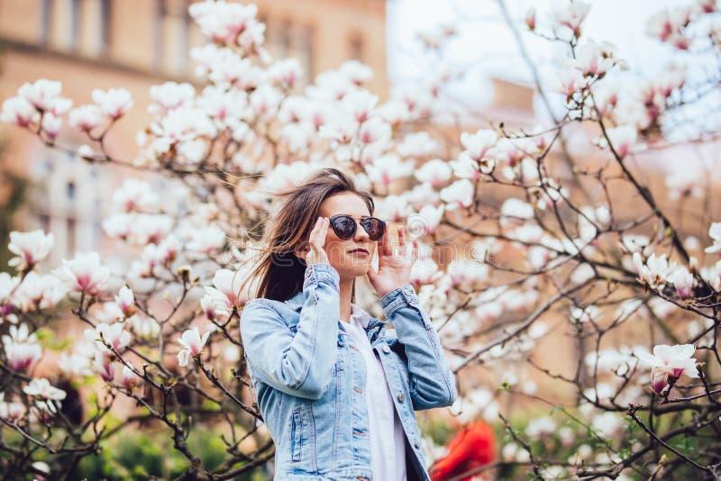 摆在与木兰的开花的树的妇女或俏丽的女孩在春天庭院里开花在晴天 免版税图库摄影