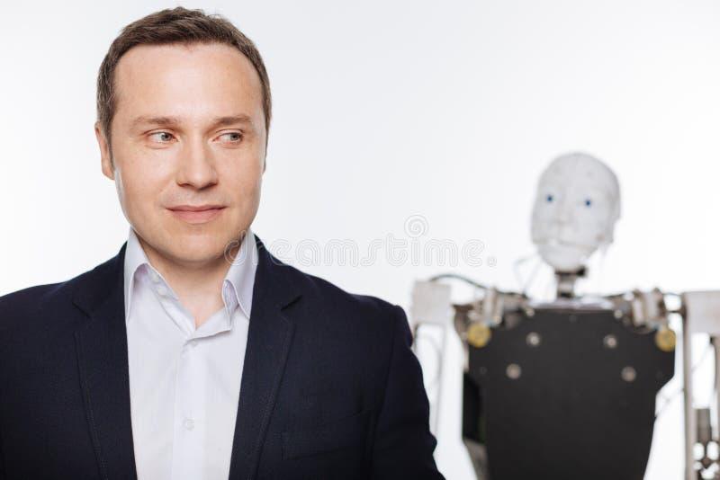 摆在与机器人的热心进步科学家 免版税图库摄影