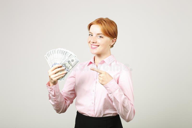 摆在与束的可爱的年轻女实业家USD现有金额显示正面情感和愉快的表情的 免版税图库摄影