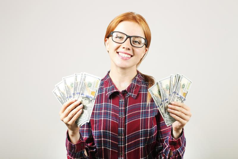 摆在与束的可爱的年轻女实业家USD现有金额显示正面情感和愉快的表情的 库存照片
