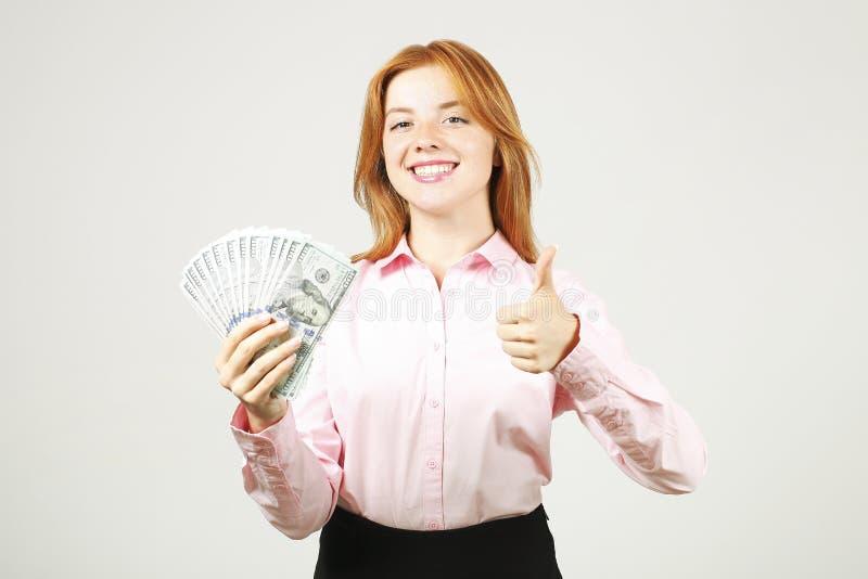摆在与束的可爱的年轻女实业家USD现有金额显示正面情感和愉快的表情的 免版税库存照片