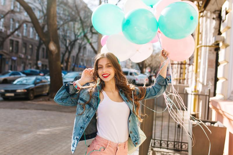 摆在与束的牛仔布夹克的迷人的微笑的女孩在城市背景的五颜六色的气球 画象卷曲 免版税库存照片