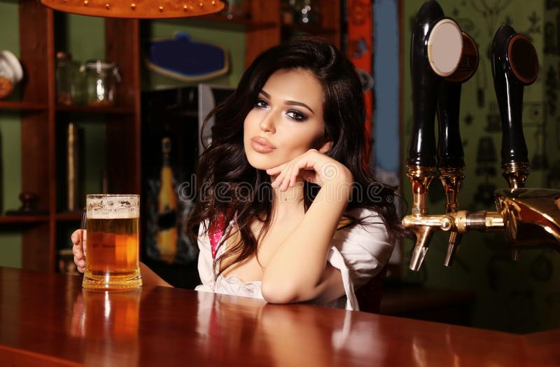 摆在与杯的酒吧柜台的妇女侍酒者啤酒 免版税库存图片