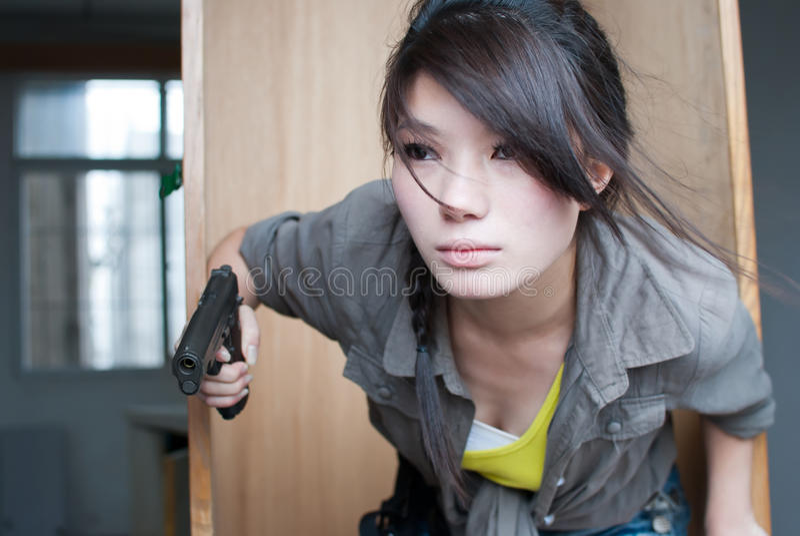摆在与枪的妇女 免版税库存图片