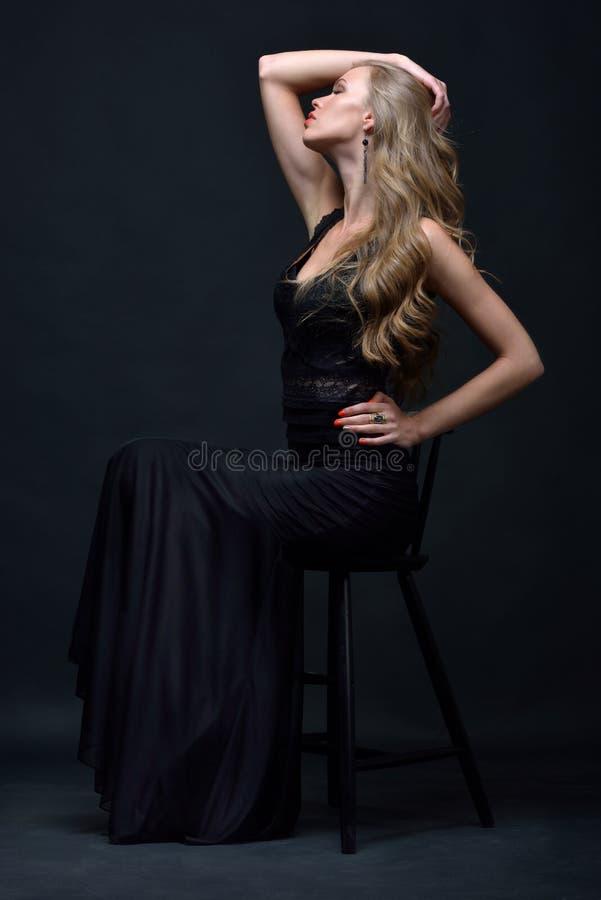 摆在与椅子的一件黑晚礼服的美丽的妇女 免版税图库摄影