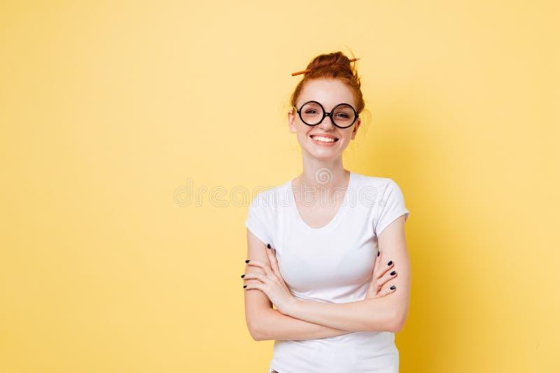 摆在与横渡的胳膊的镜片的微笑的姜妇女 免版税库存照片