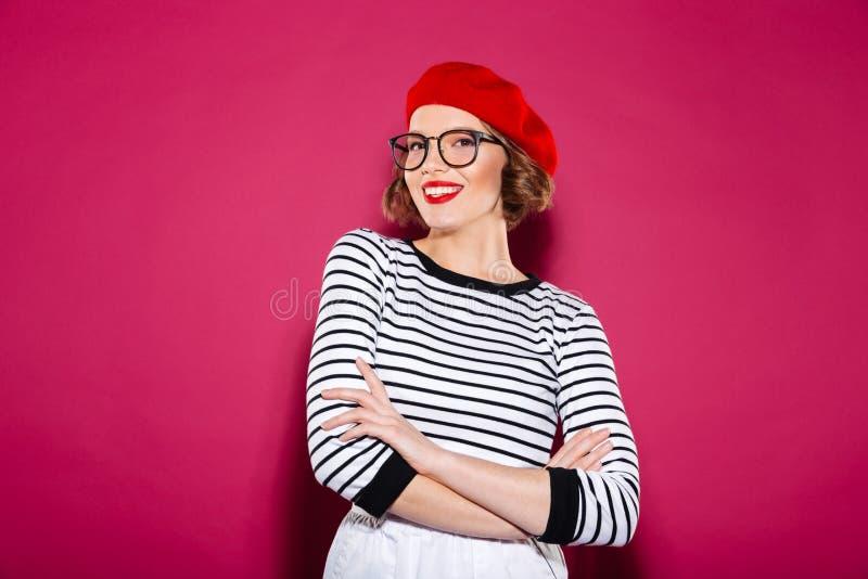 摆在与横渡的胳膊的镜片的微笑的姜妇女 免版税库存图片