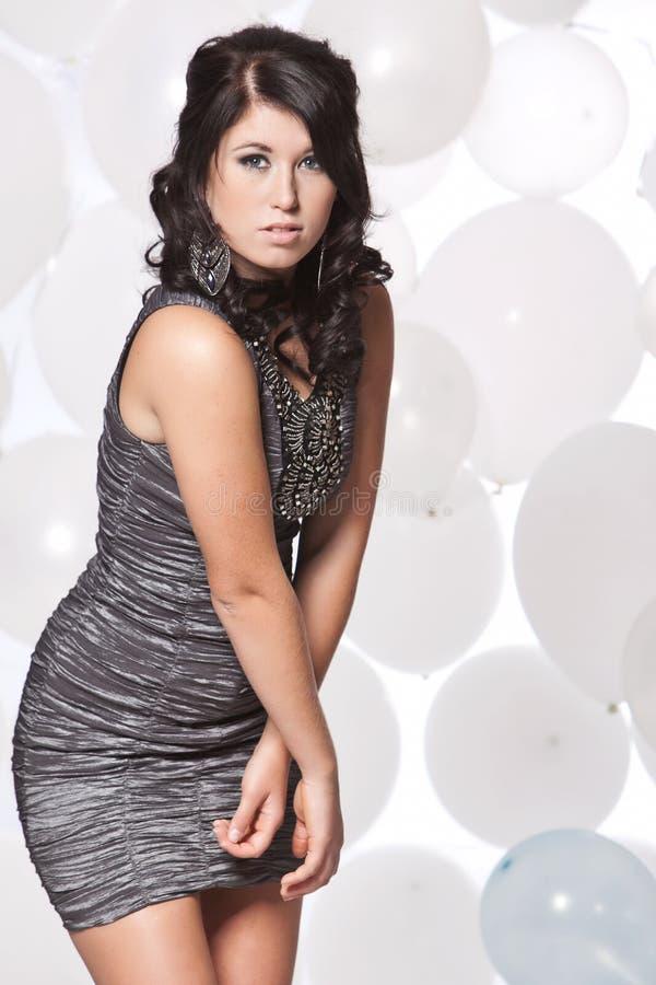 摆在与气球backgro的女性时装模特儿 免版税库存照片