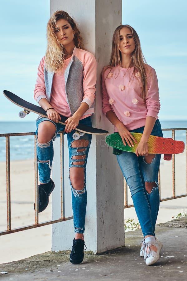 摆在与滑板的时髦衣裳的两个美丽的女孩在栏杆附近反对沿海 图库摄影