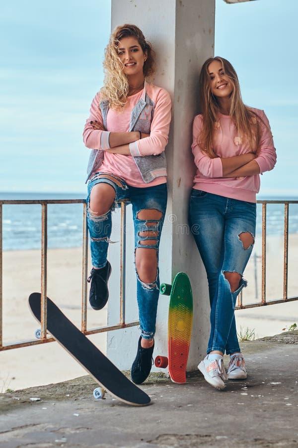 摆在与滑板的时髦衣裳的两个美丽的女孩在栏杆附近反对沿海 免版税库存图片