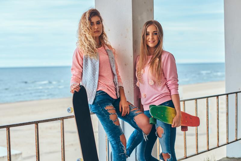 摆在与滑板的时髦衣裳的两个美丽的女孩在栏杆附近反对沿海 免版税图库摄影