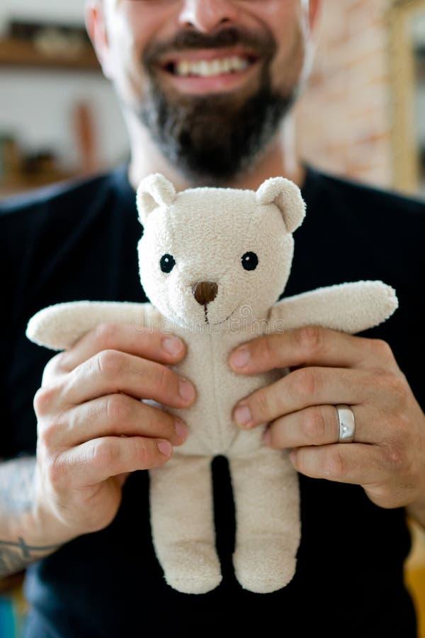 摆在与玩具熊的黑T恤杉的成人人 免版税库存图片