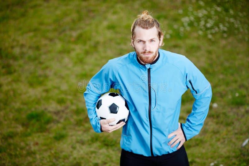 摆在与球的年轻确信的教练画象在足球场 图库摄影