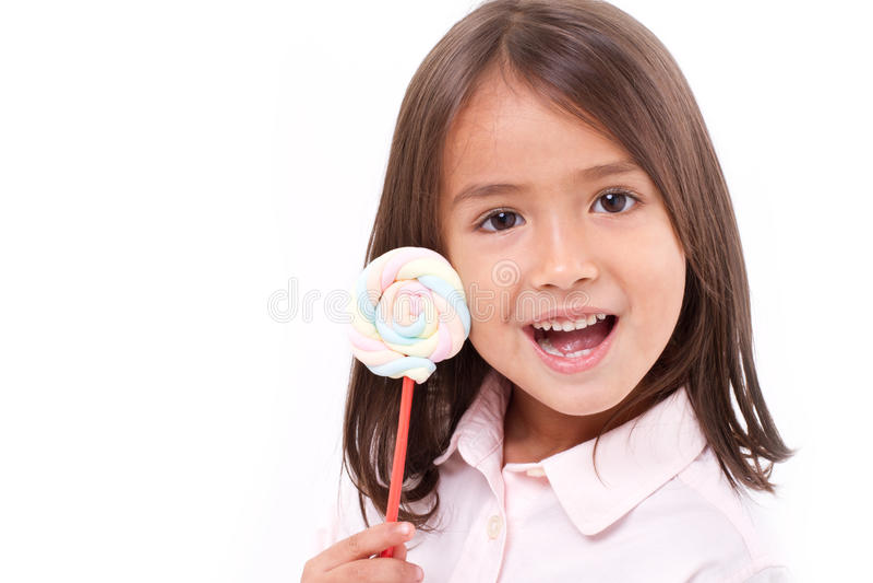 摆在与甜淡色的嬉戏的逗人喜爱的小女孩marshmal 免版税库存照片
