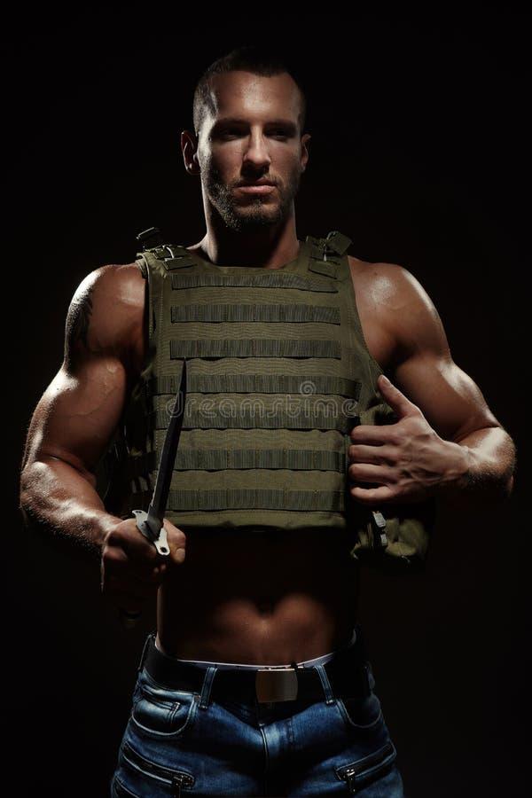 摆在与生存刀子的作战背心的军事样式肌肉人 免版税库存照片