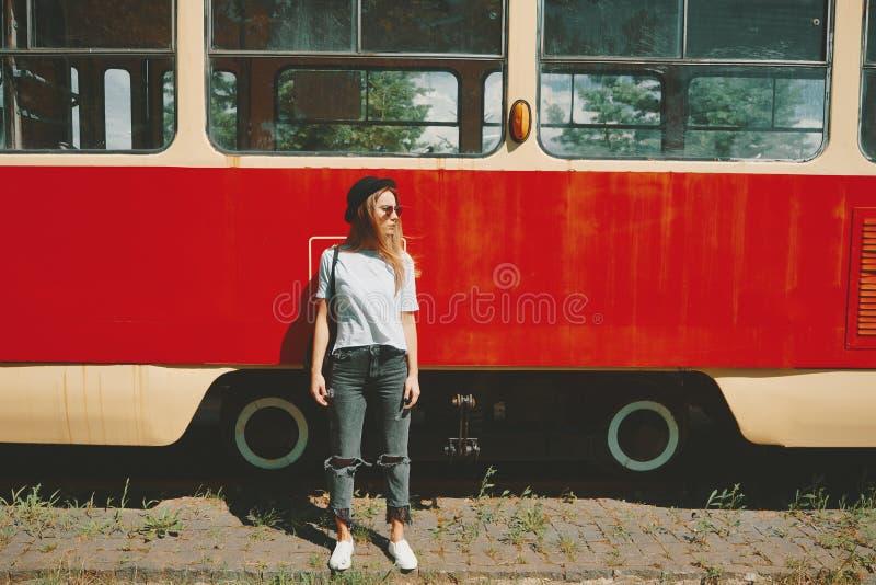 摆在与电车的无忧无虑的行家女孩在背景中 图库摄影