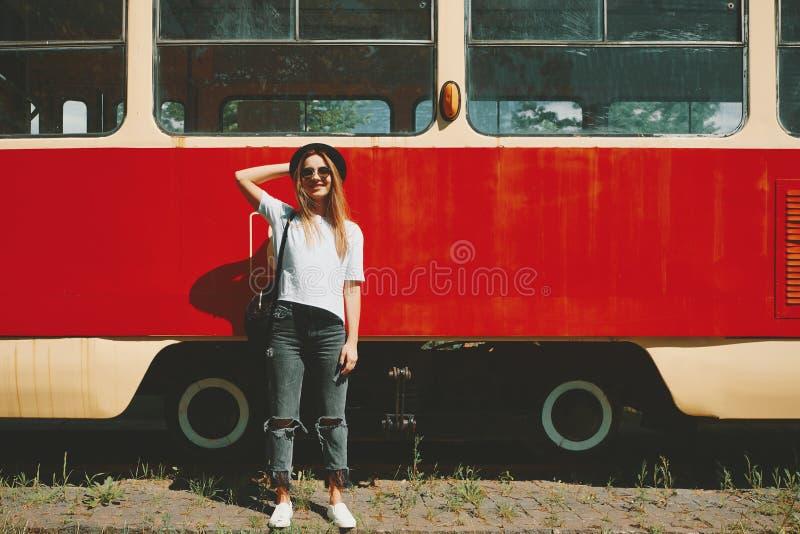 摆在与电车的无忧无虑的行家女孩在背景中 库存照片