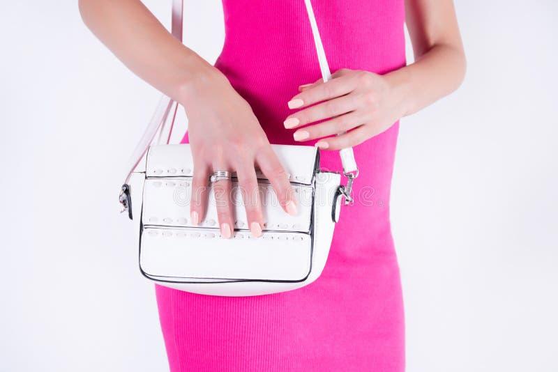 摆在与白色提包和桃红色礼服的年轻可爱的女孩 免版税库存照片