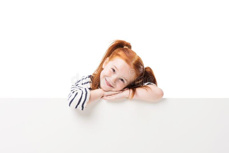 摆在与空白的横幅的可爱的愉快的矮小的红头发人女孩 免版税库存照片