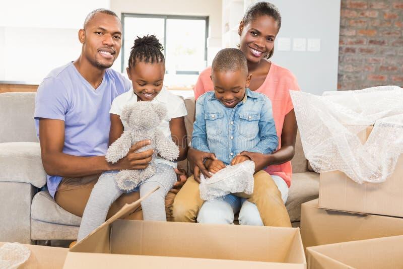 摆在与箱子的偶然愉快的家庭 免版税库存照片