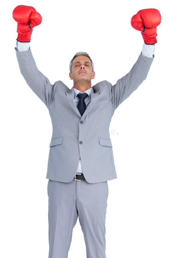 摆在与红色拳击手套的神气活现的商人 免版税库存图片