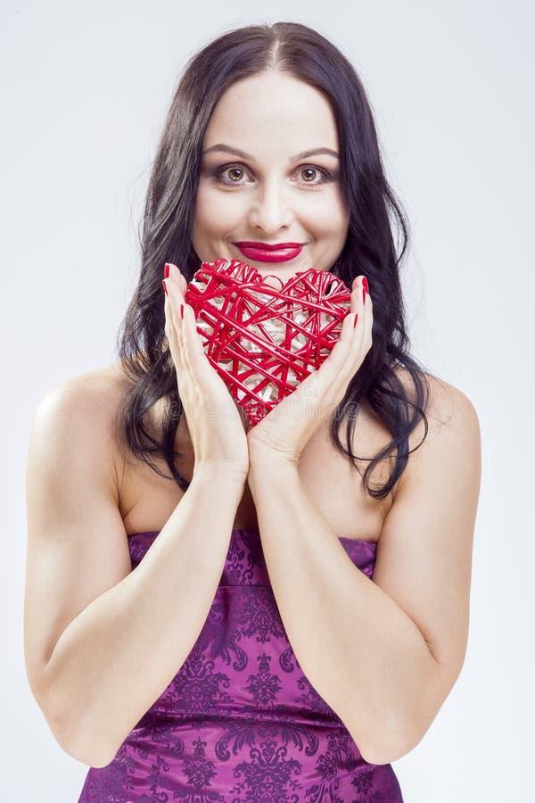 摆在与红色柳条心脏的成熟白种人妇女画象  图库摄影