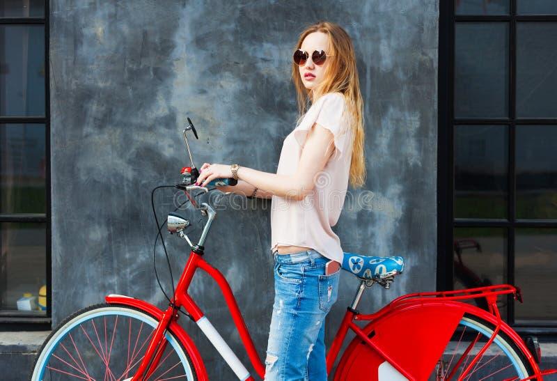 摆在与红色葡萄酒自行车的美丽的长腿的女孩 她有一个智能手机在她的牛仔裤口袋 库存照片
