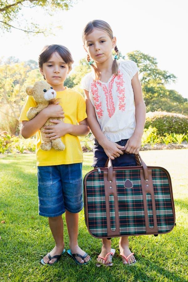 摆在与老行李和玩具熊的逗人喜爱的兄弟和姐妹画象  图库摄影