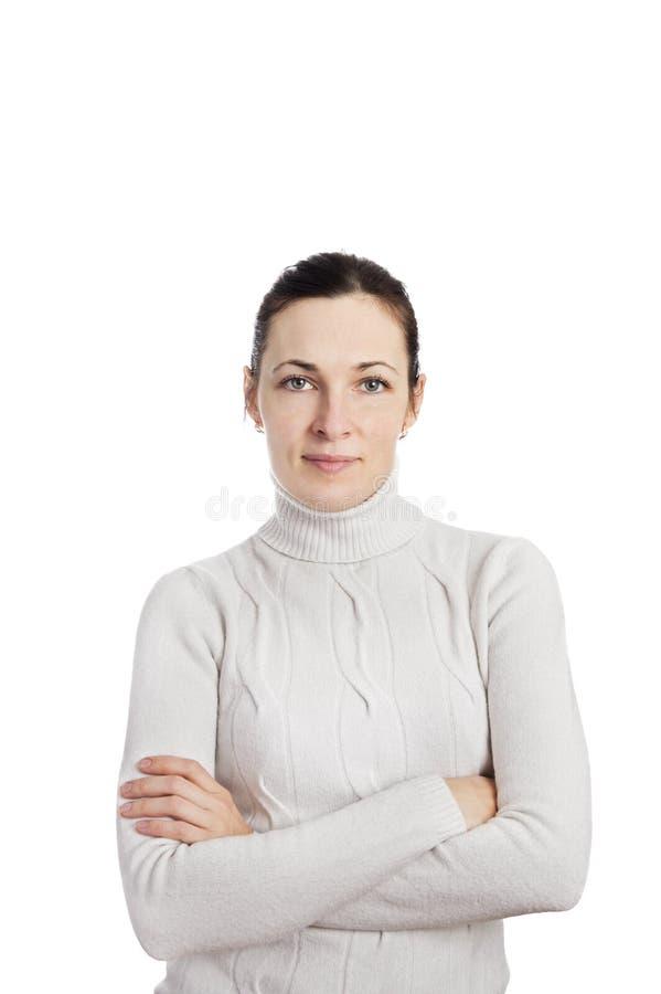 摆在与胳膊的妇女佩带的白色毛线衣的画象 免版税图库摄影