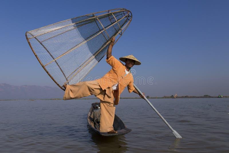 摆在与脚的缅甸渔夫拿着他圆锥形的捕鱼网, Inle湖,掸邦,缅甸 免版税库存照片