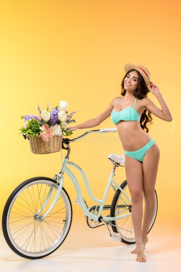 摆在与自行车和花的比基尼泳装的美丽的亭亭玉立的女孩, 免版税图库摄影