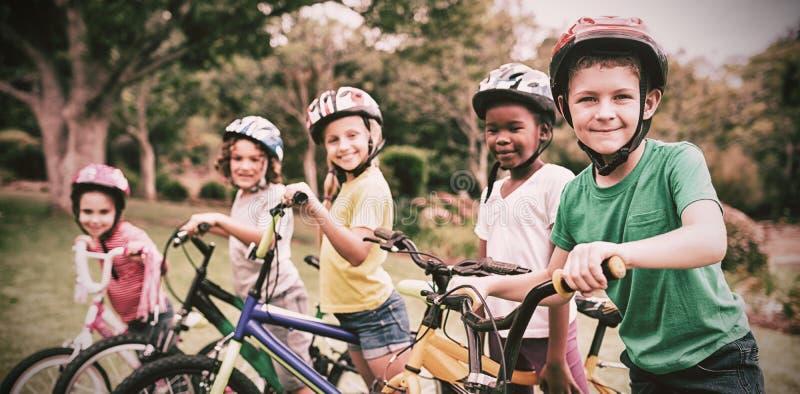 摆在与自行车的微笑的孩子 库存图片