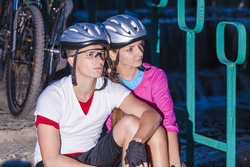 摆在与自行车的盔甲的两个骑自行车者户外 库存照片