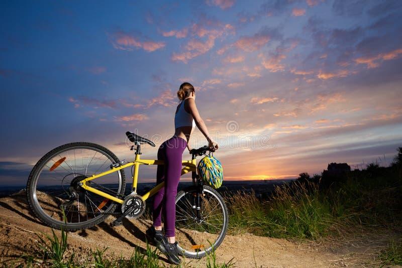 摆在与自行车的紫罗兰色绑腿的运动的妇女 库存图片