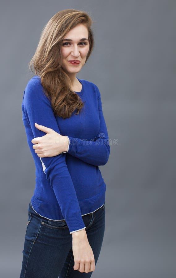摆在与舒适的软软地被交叉的双臂的可爱的少妇 免版税库存照片