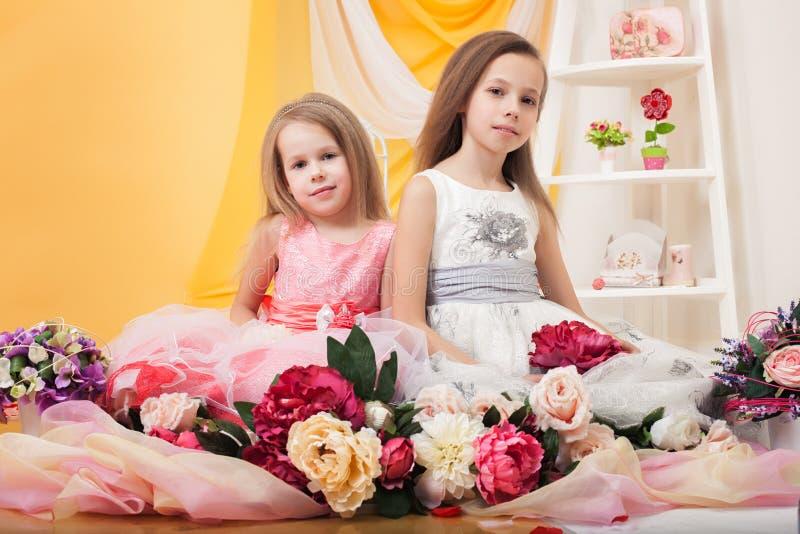 摆在与花的俏丽的孪生在演播室 库存图片