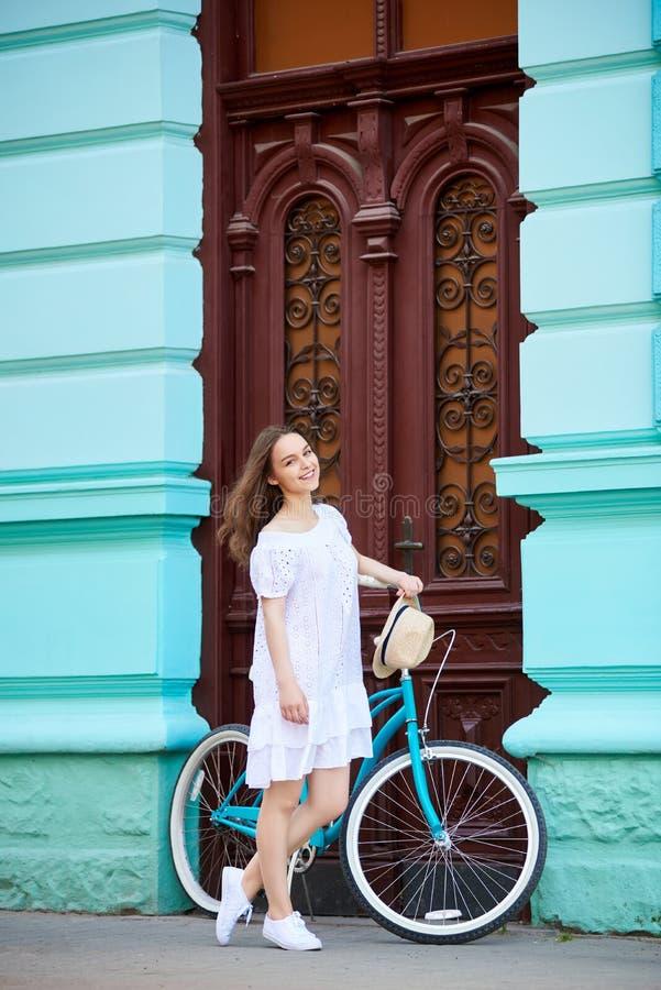 摆在与草帽的白色礼服的微笑的可爱的女性在老蓝色大厦前面的蓝色葡萄酒自行车旁边 库存图片