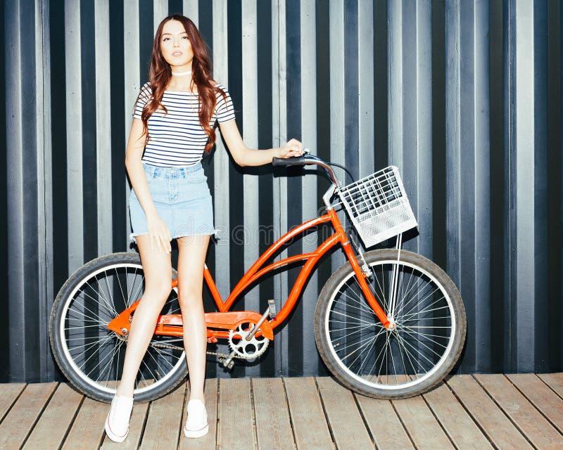 摆在与葡萄酒红色自行车的夏天成套装备的美丽的长发女孩亚洲人 夜射击 免版税库存图片