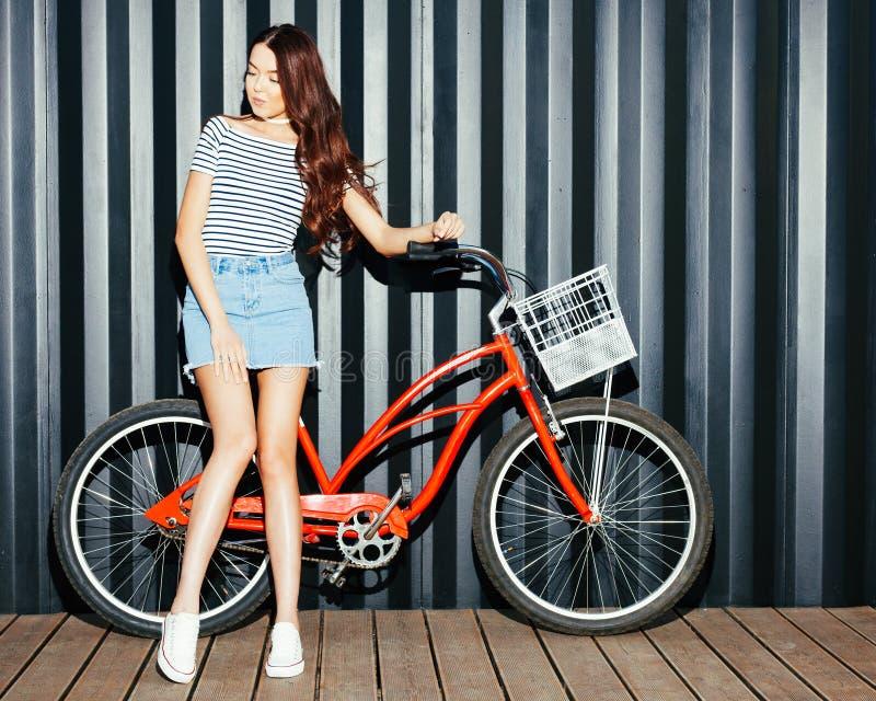 摆在与葡萄酒红色自行车的夏天成套装备的美丽的长发腿长的女孩亚洲人 夜射击 看照相机 库存图片